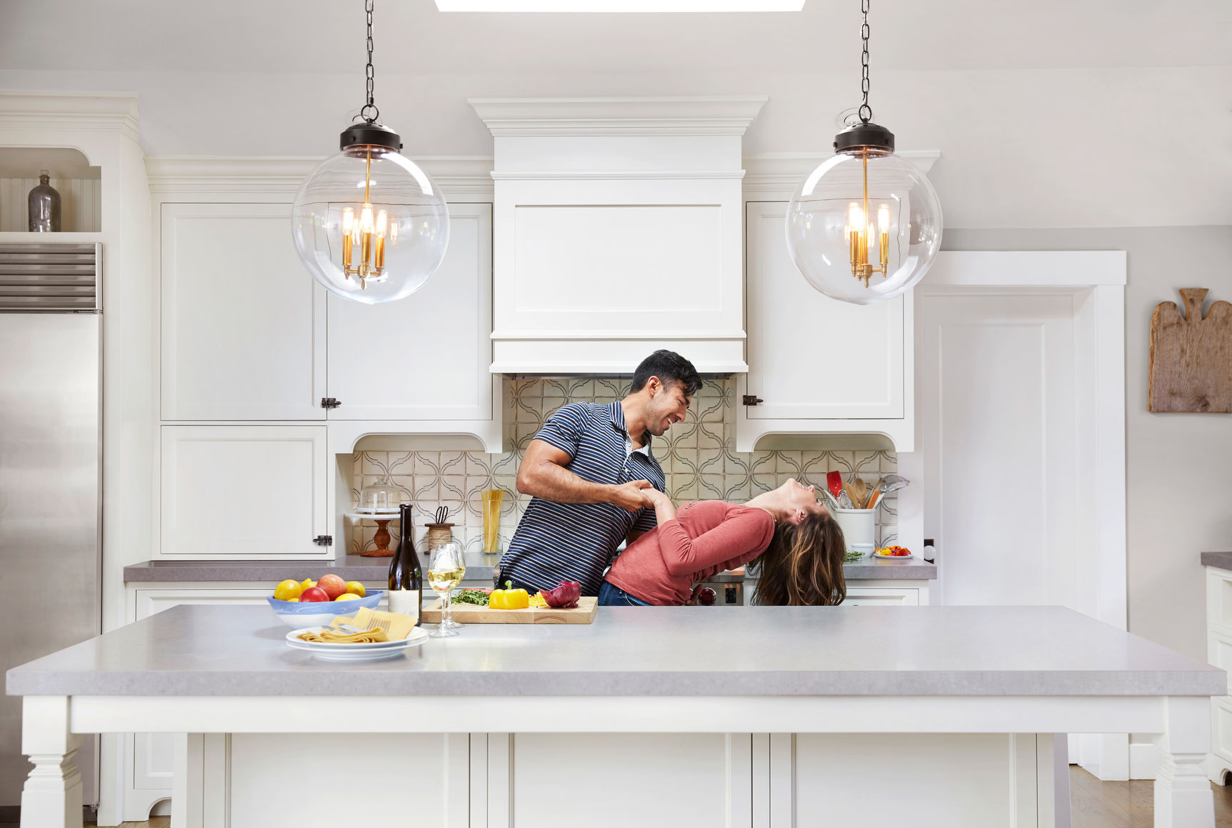 Young couple dancing together while cooking in the kitchen