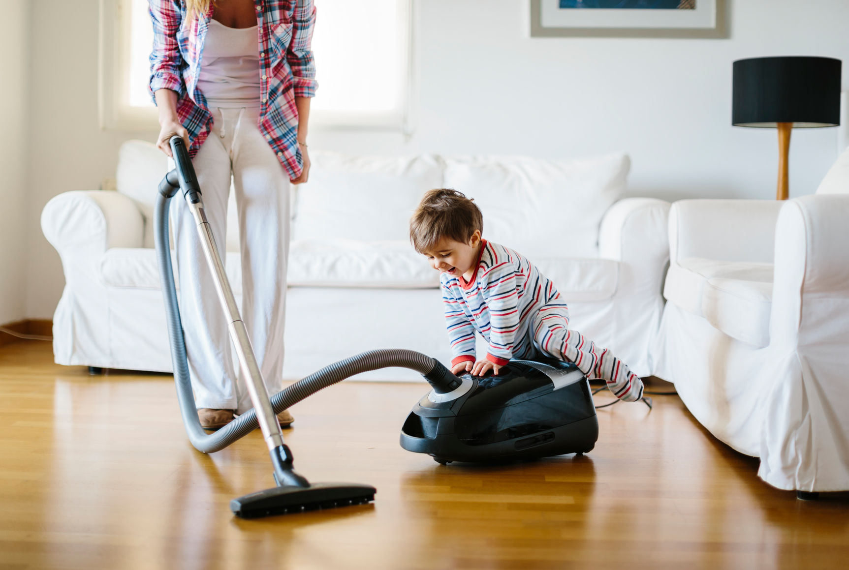 Young boy riding on the vacuum his mother is using in their living room.