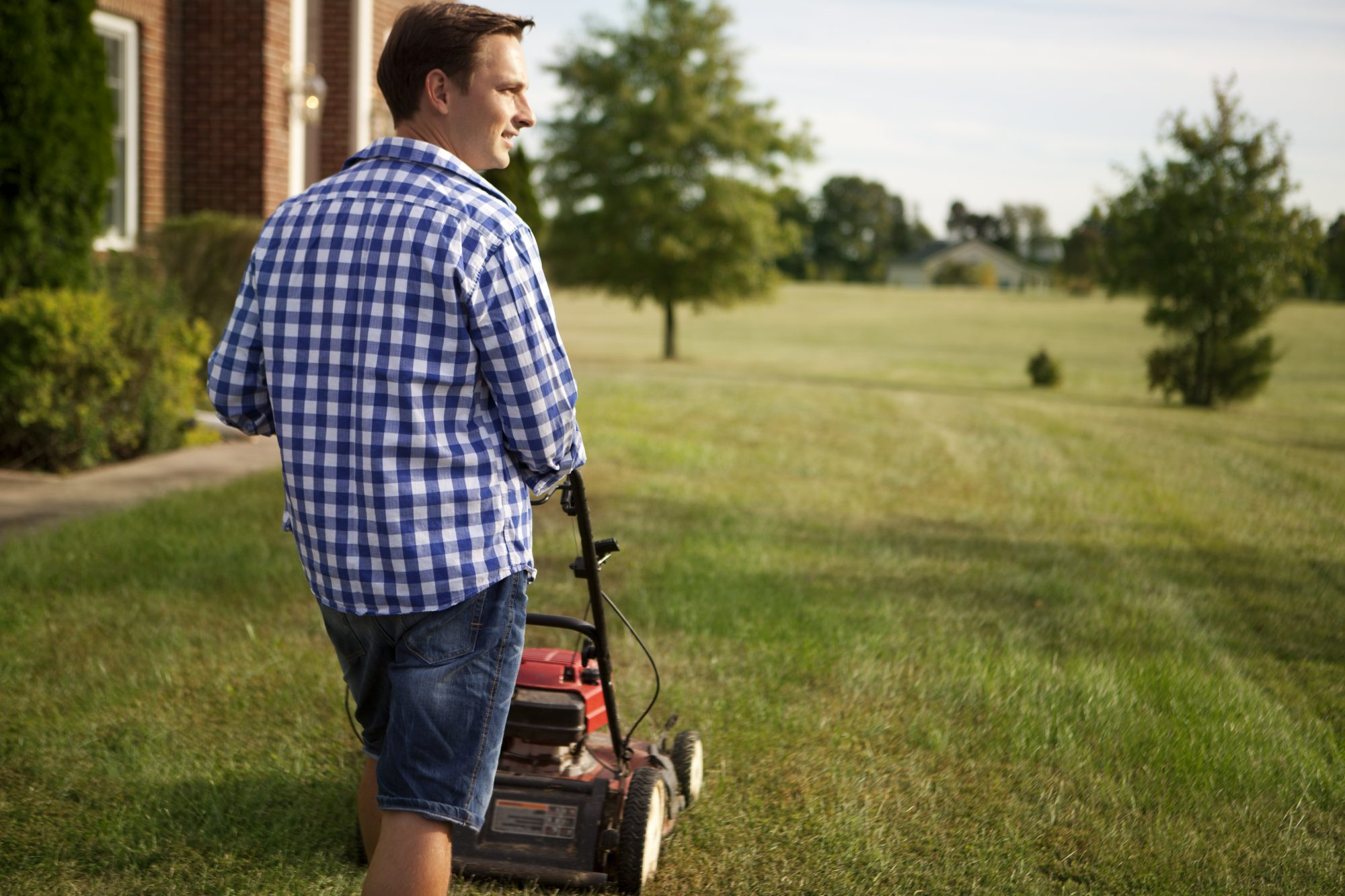 Young man mowing the lawn on a sunny summer day.