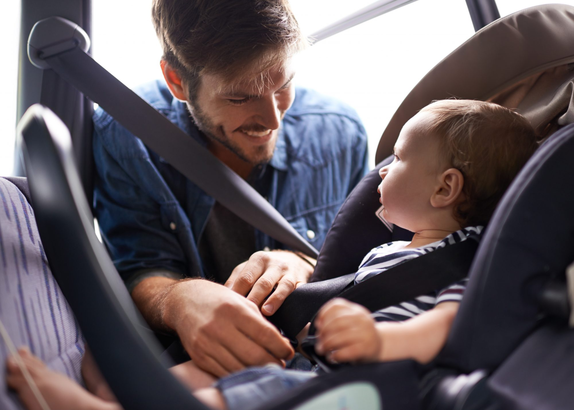 Young father smiles while he buckles his baby into car seat.
