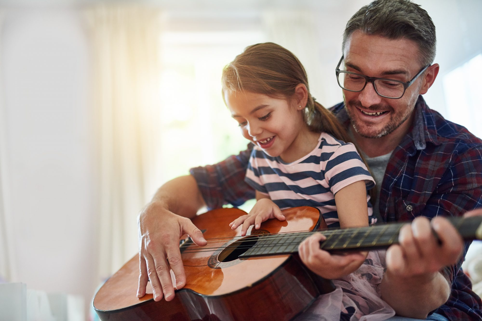 Father and daughter playing the guitar together.