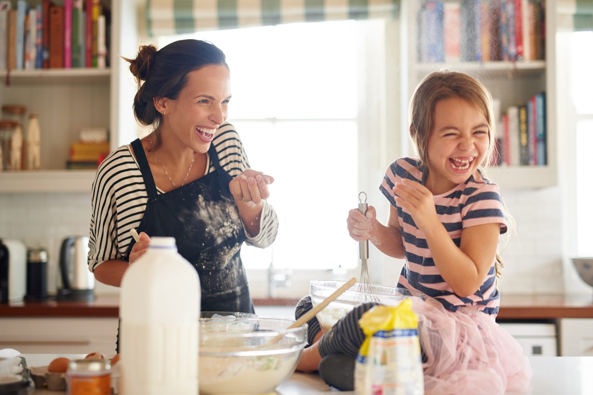 Mother and daughter happily baking in kitchen.