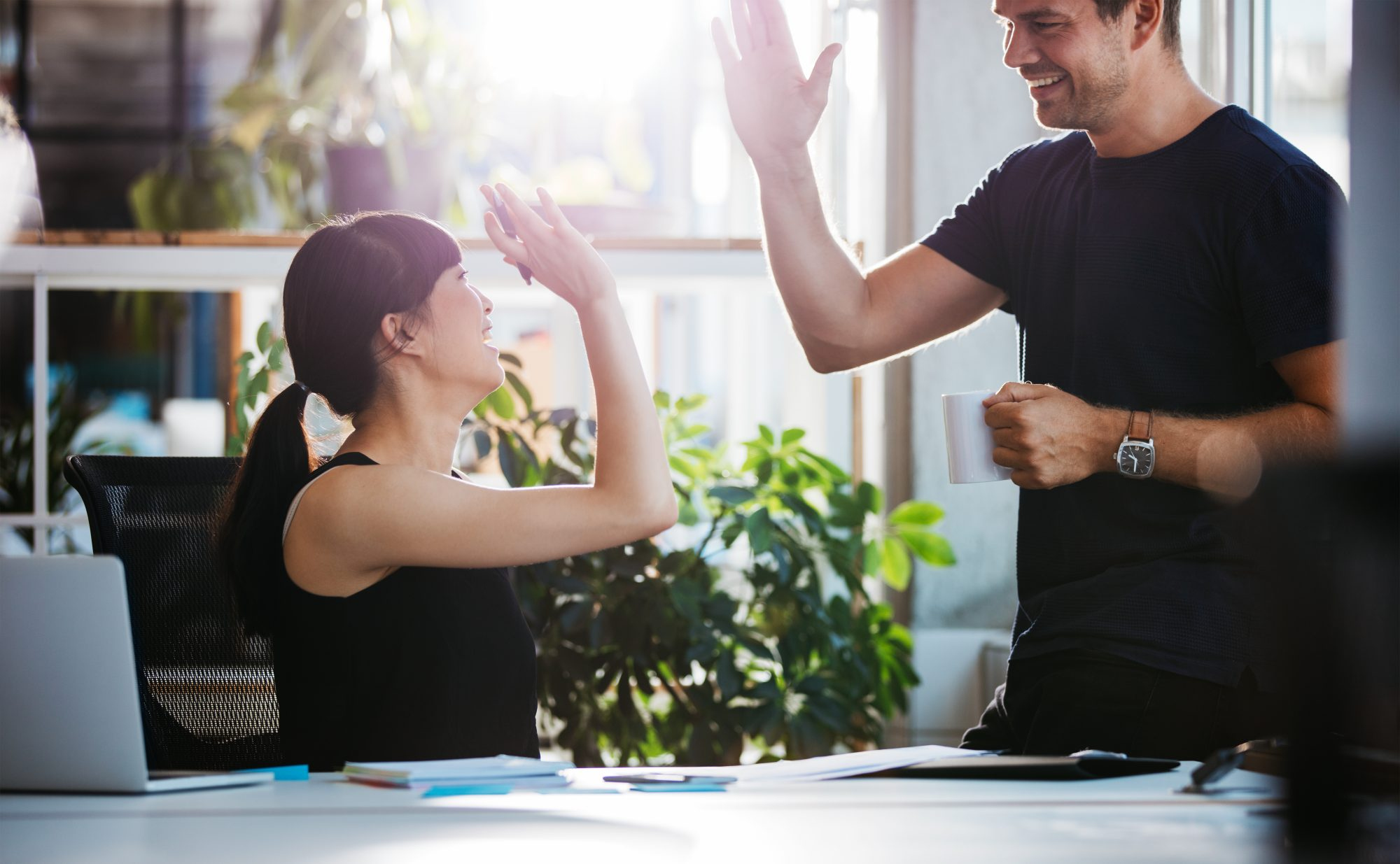 Man and woman giving a high-five in an office setting.