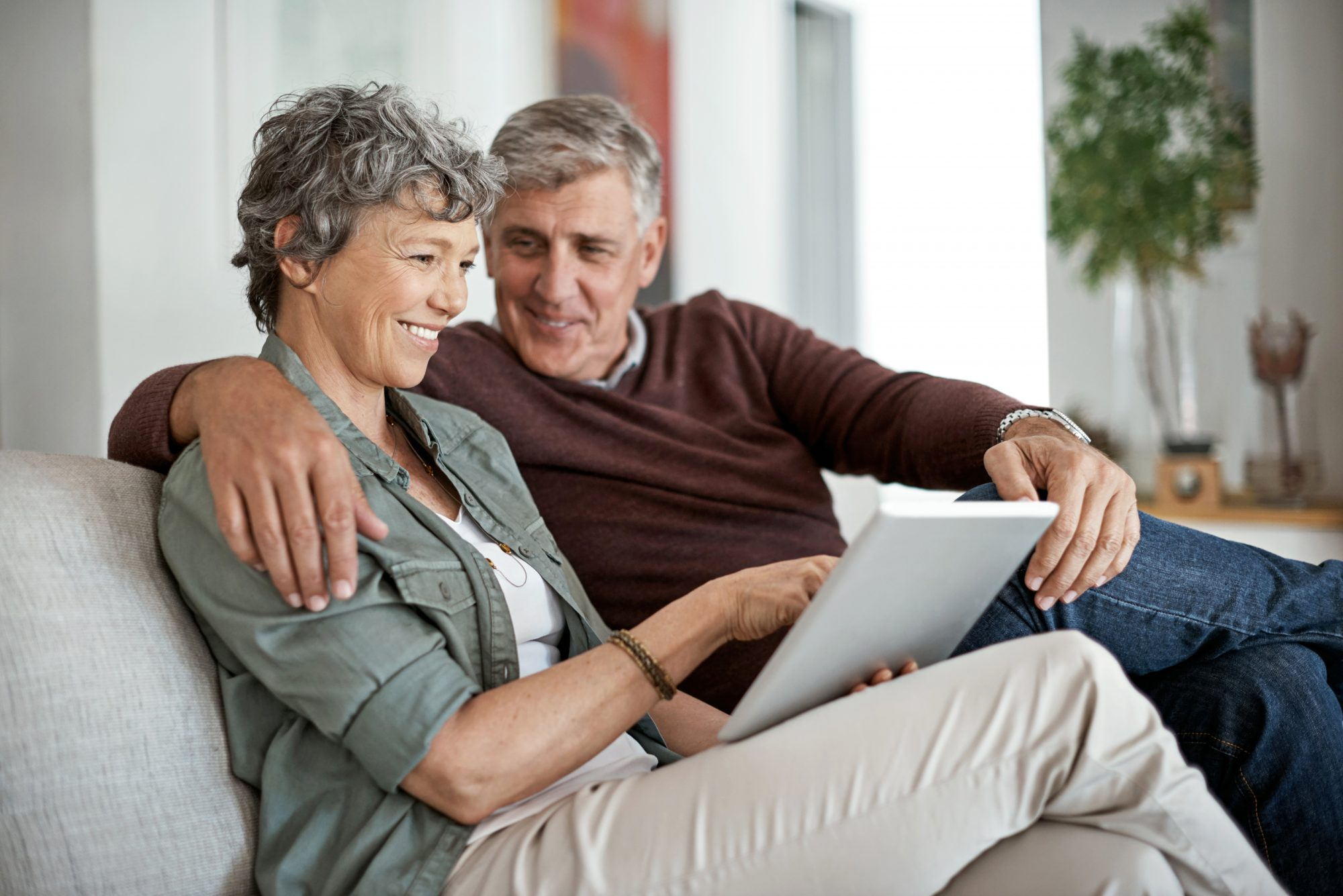 Mature man has his arm wrapped around Mature couple sit on the couch together and review their financials.wife while they sit on the couch together and review their financials.