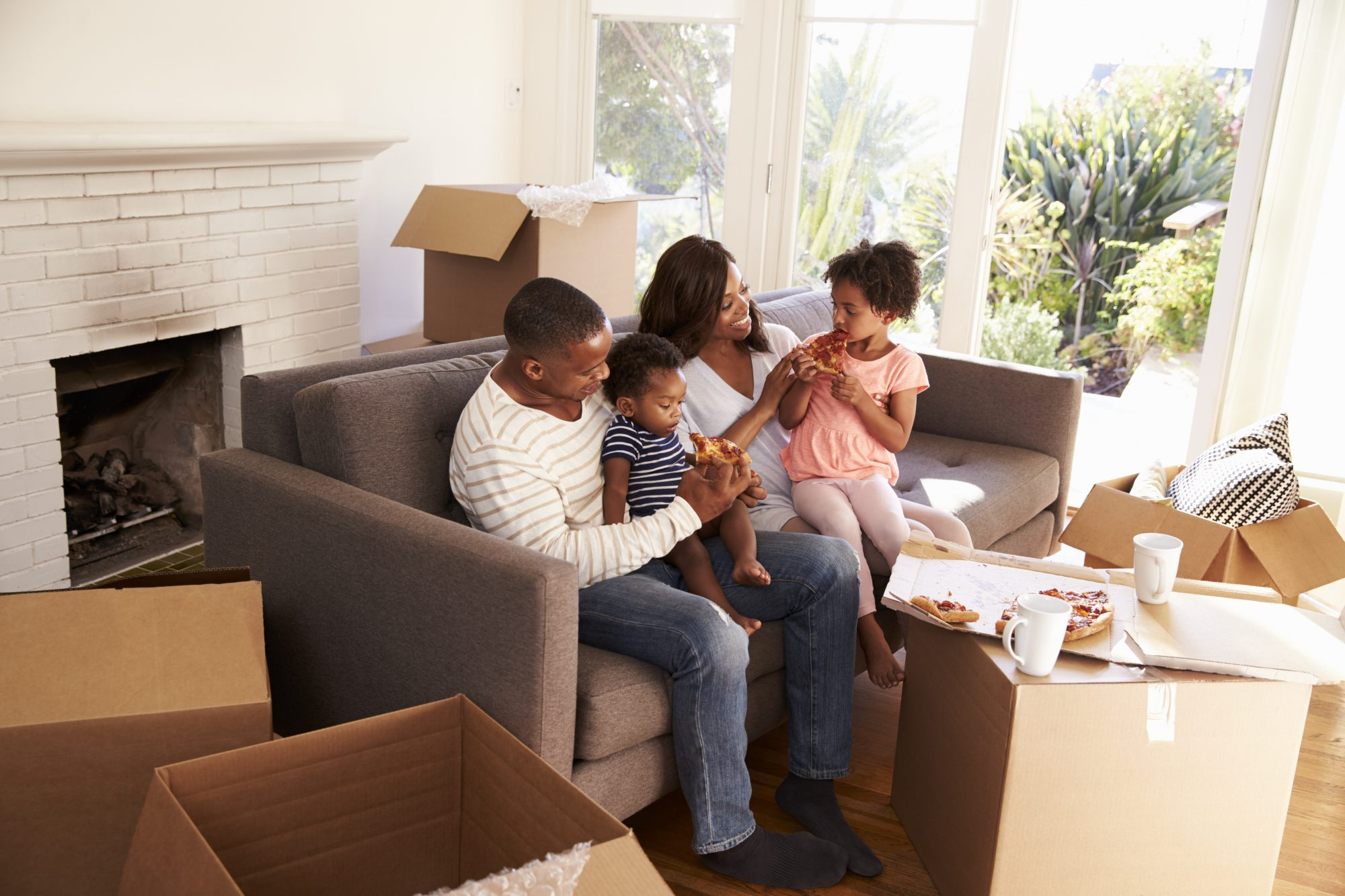 Young family enjoys eating their first dinner together in their new home with unpacked boxes surrounding them.