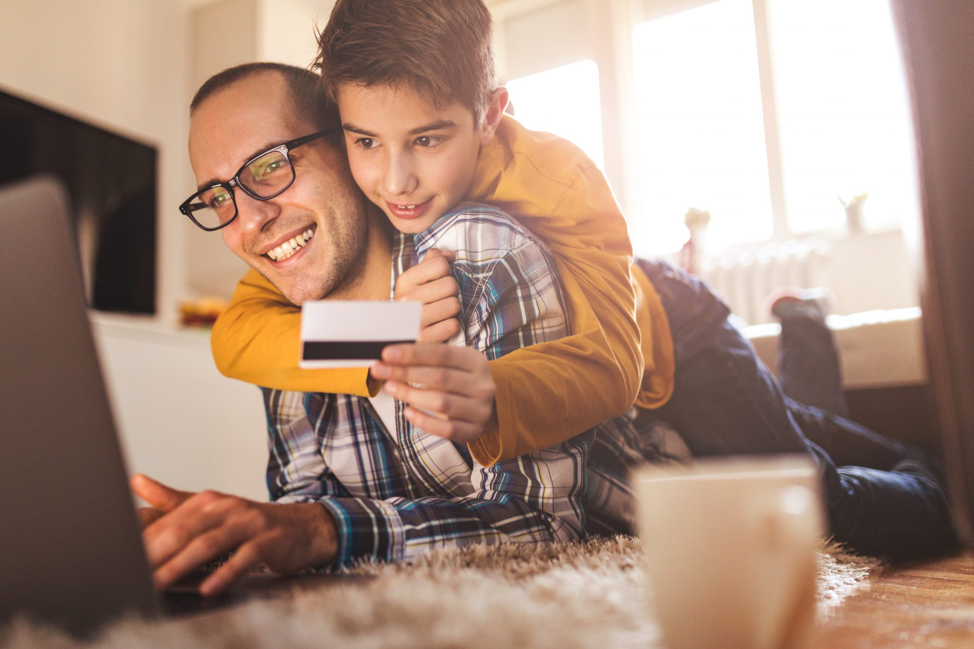 Son holding credit card while on father's back.