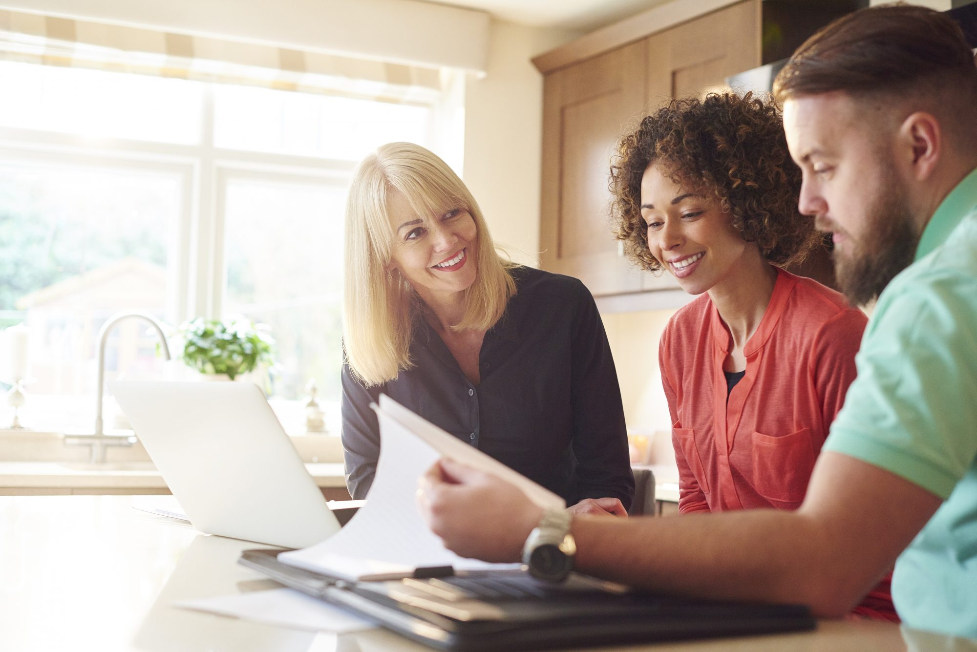 #2 Insurance agent reviews insurance policy with young couple in their home.