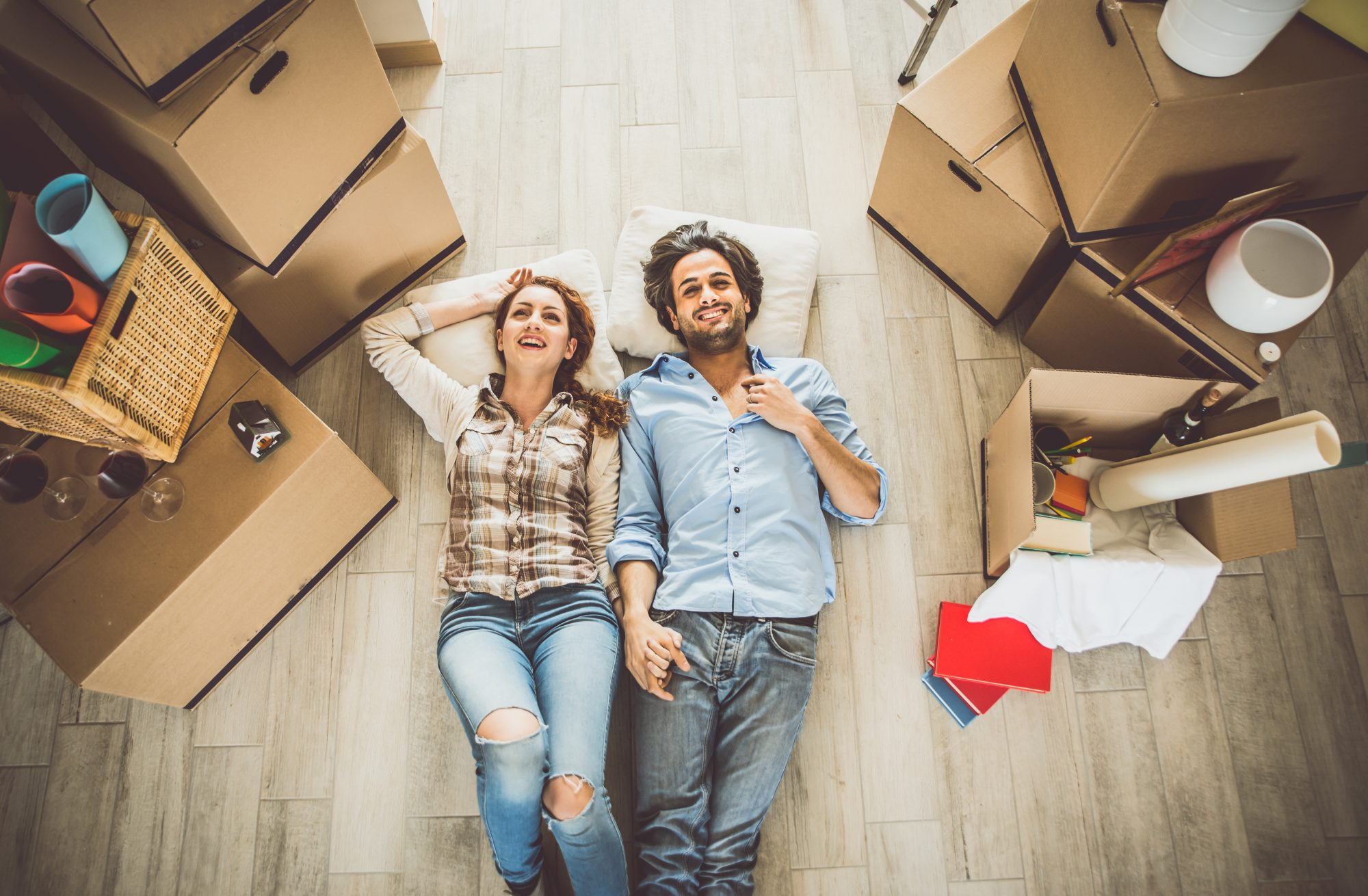 Couple take a break from packing to rest on floor surrounded by unpacked boxes.