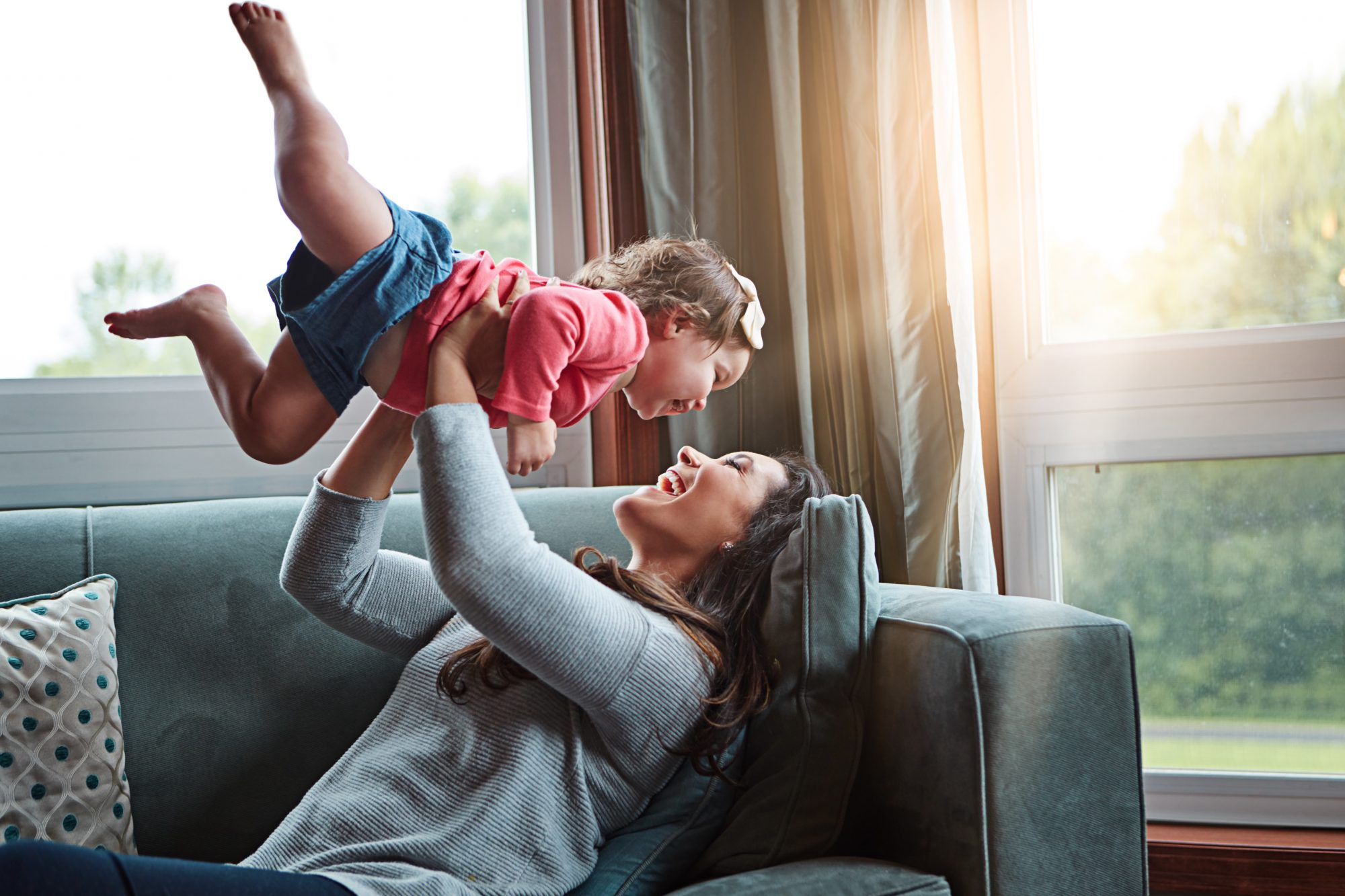 Mother lies on couch while holding baby up in the air and smiling.