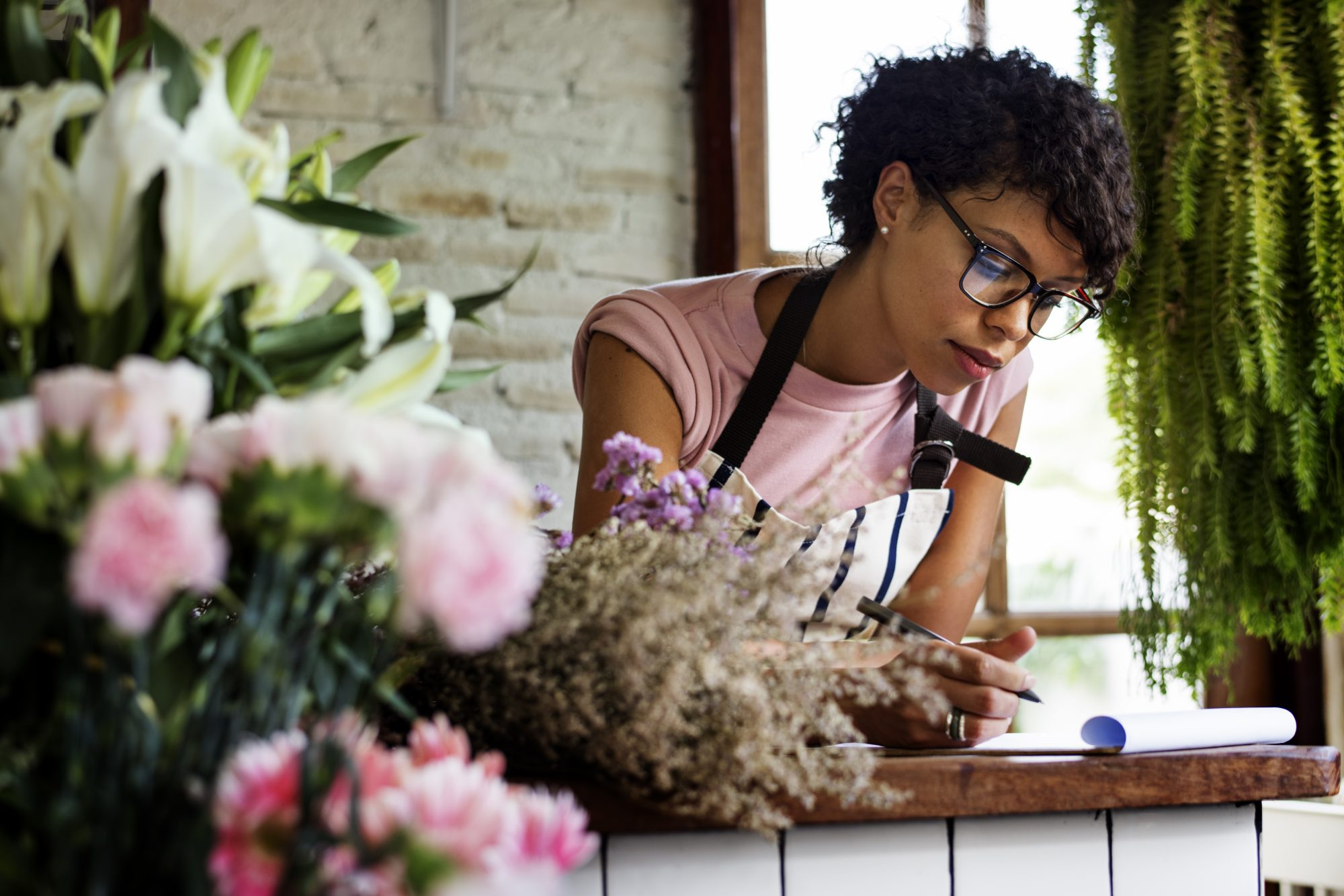 Young African American women writing in notepad in flower shop