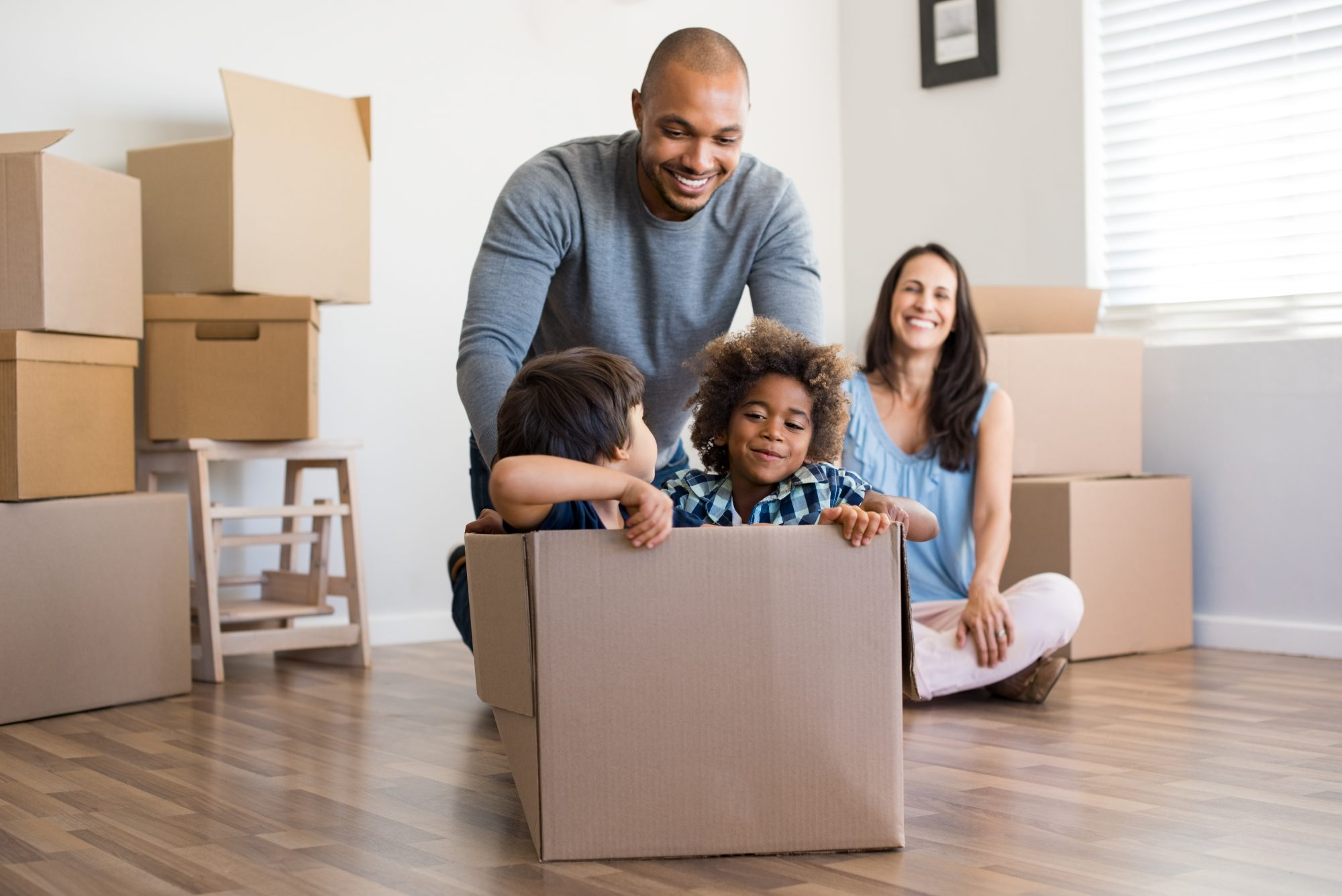 Man pushing two kids in an empty box in the living room while mom watches from a distance.