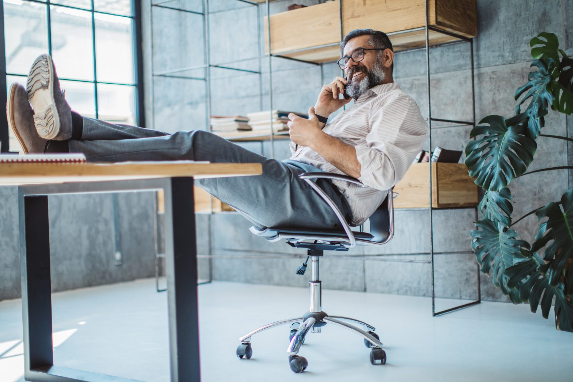 Man props feet on desk while talking on his phone in the office.