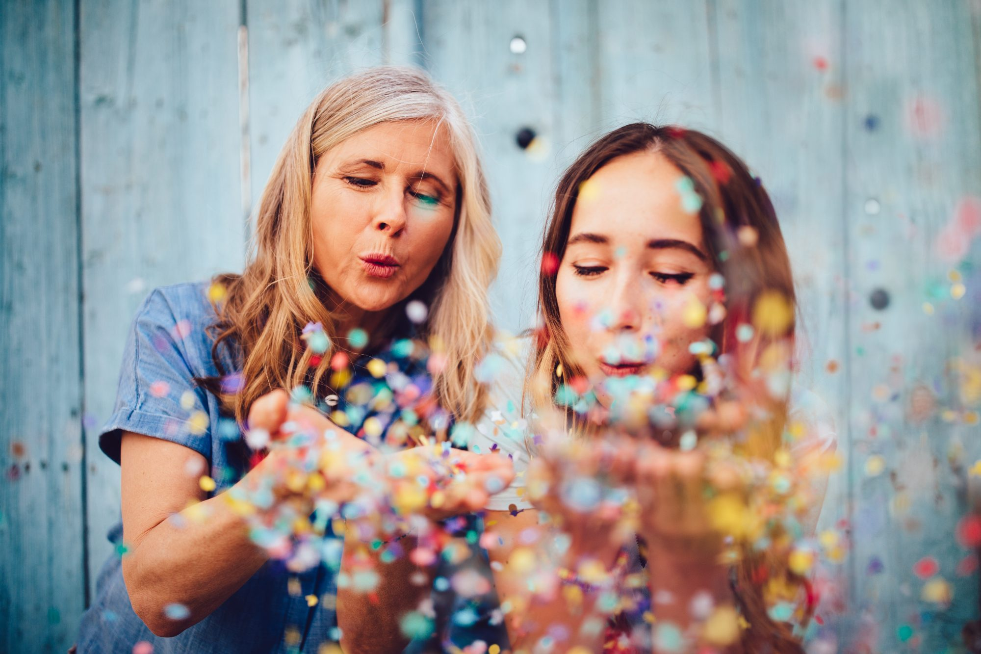 Two women blow confetti into the air in celebration.