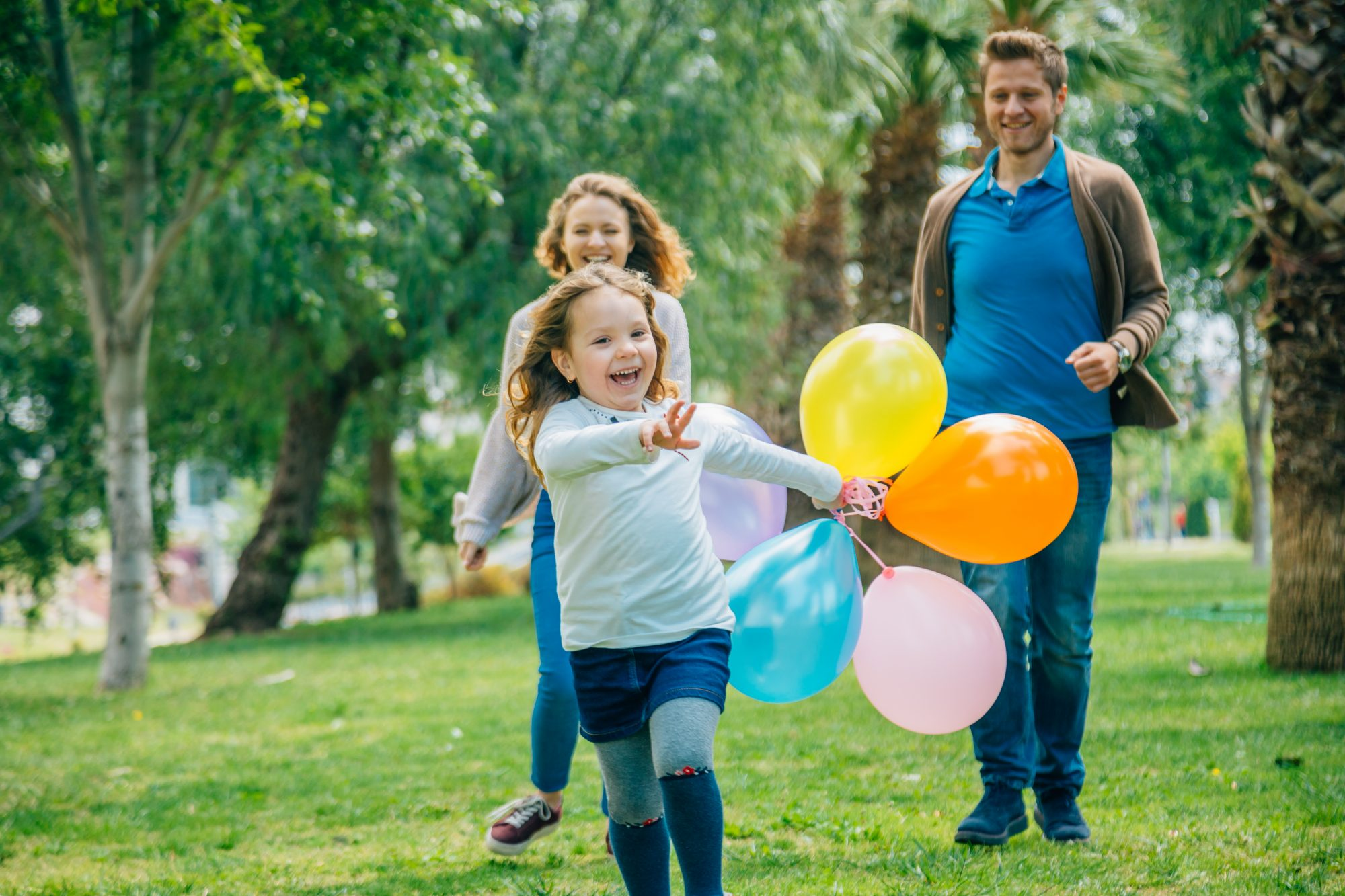 Mother and father watching daughter run with balloons.