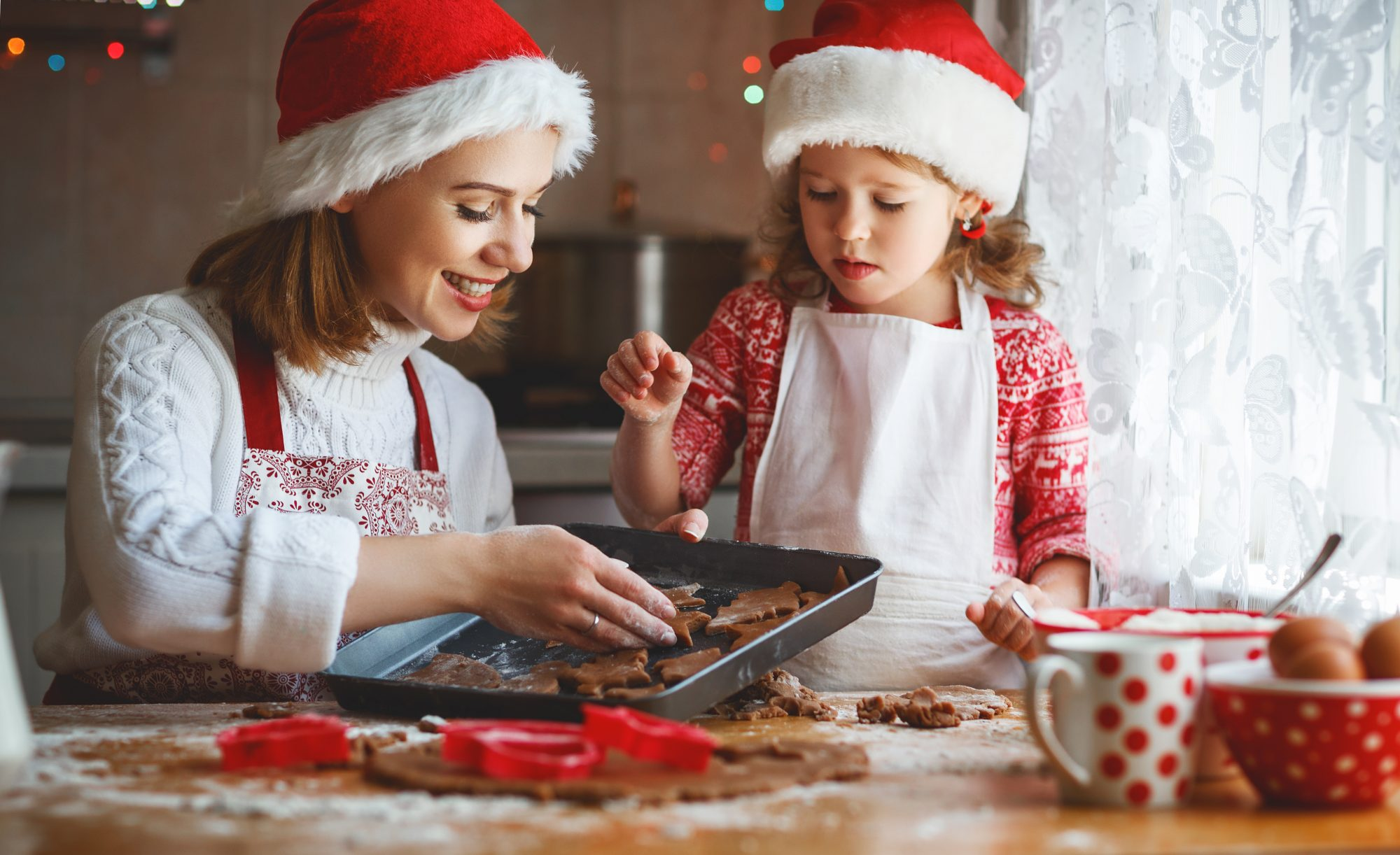 Mom and young daughter bake gingerbread cookies around the holidays.