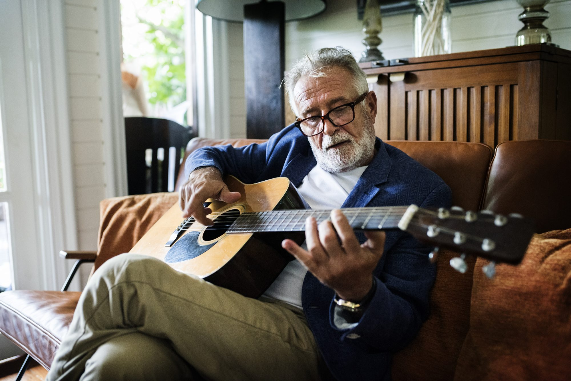 Mature man playing the guitar in his home.