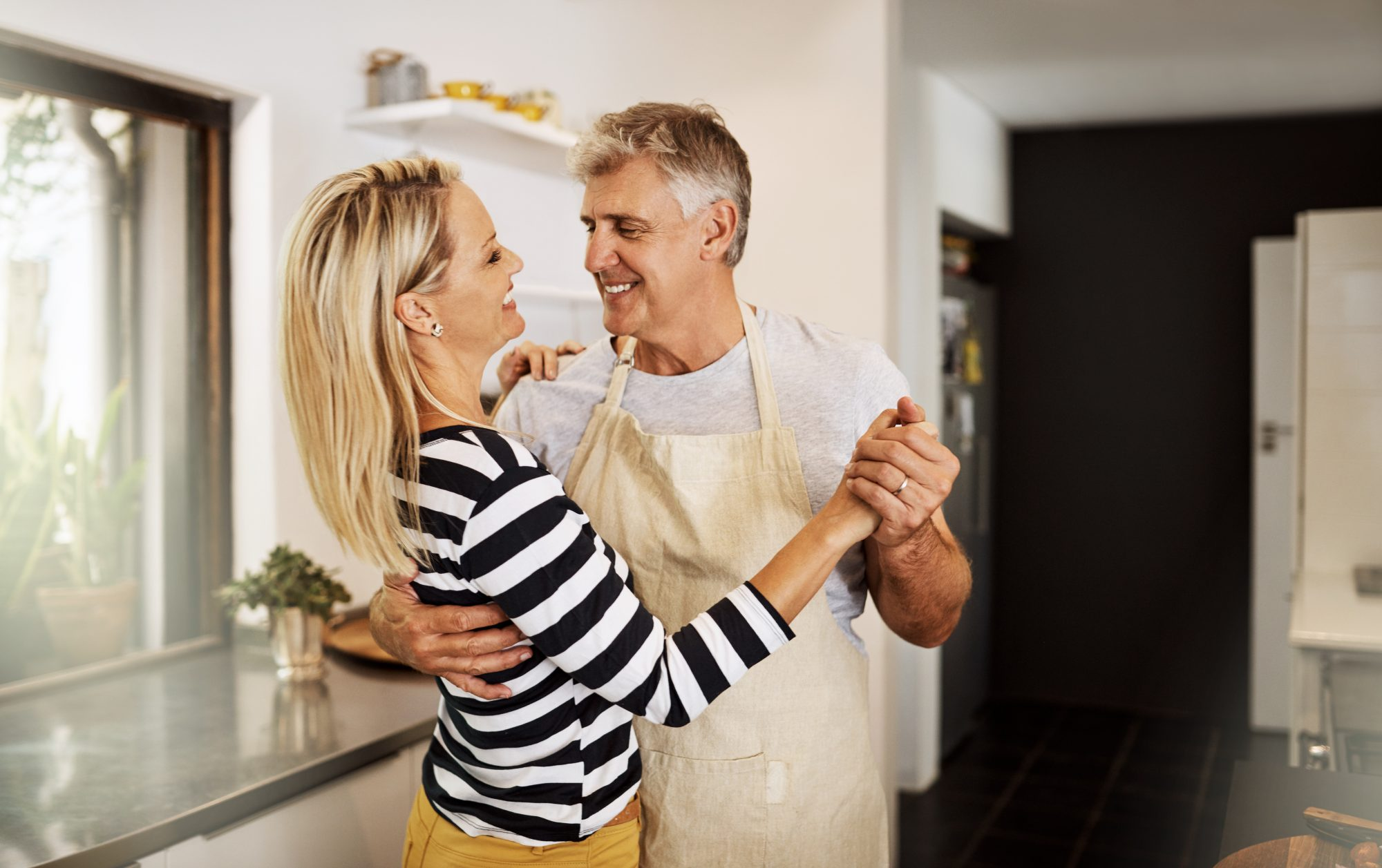 Middle aged man and woman holding hands while dancing in the newly remodeled kitchen.