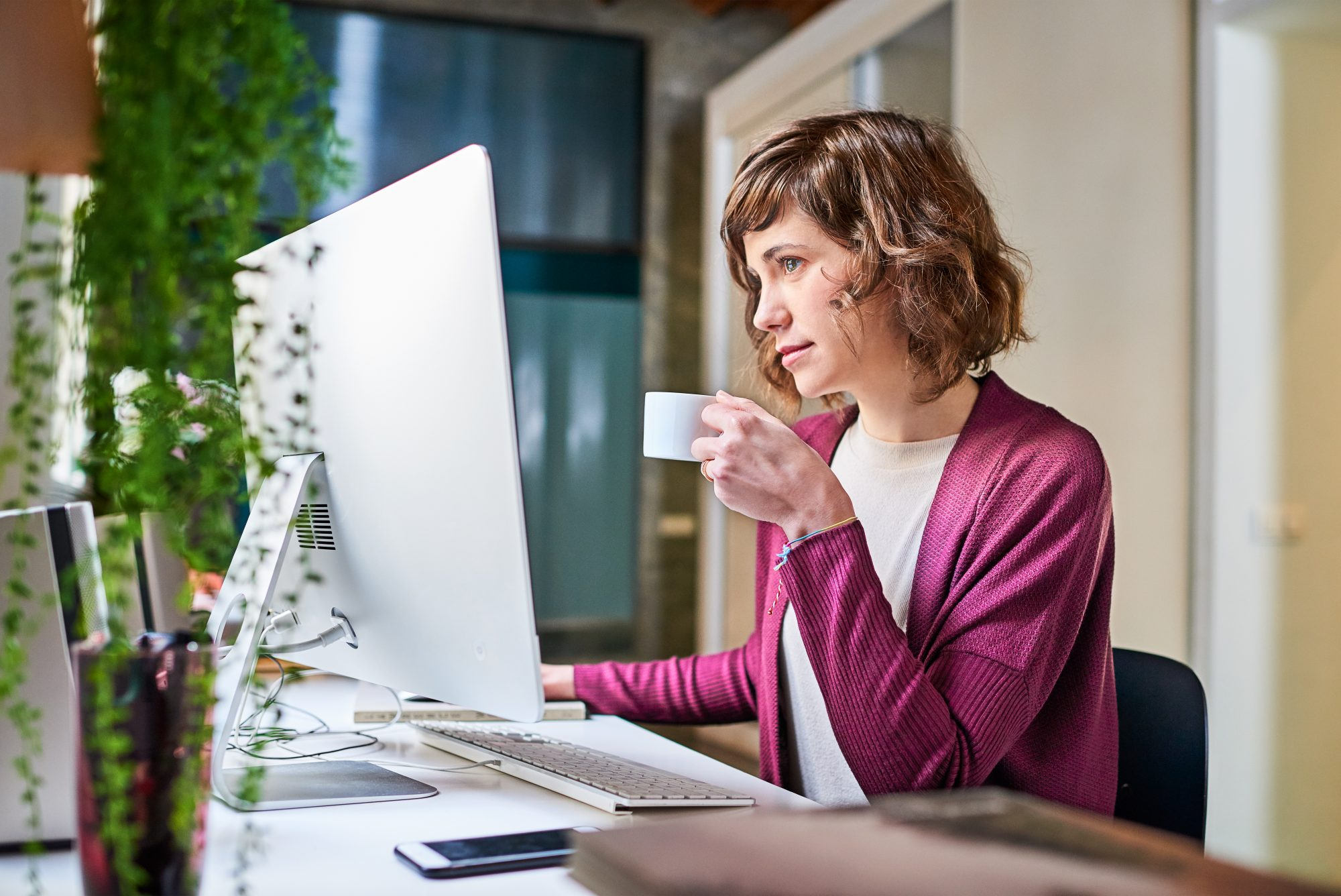 Woman drinking coffee while searching the web.