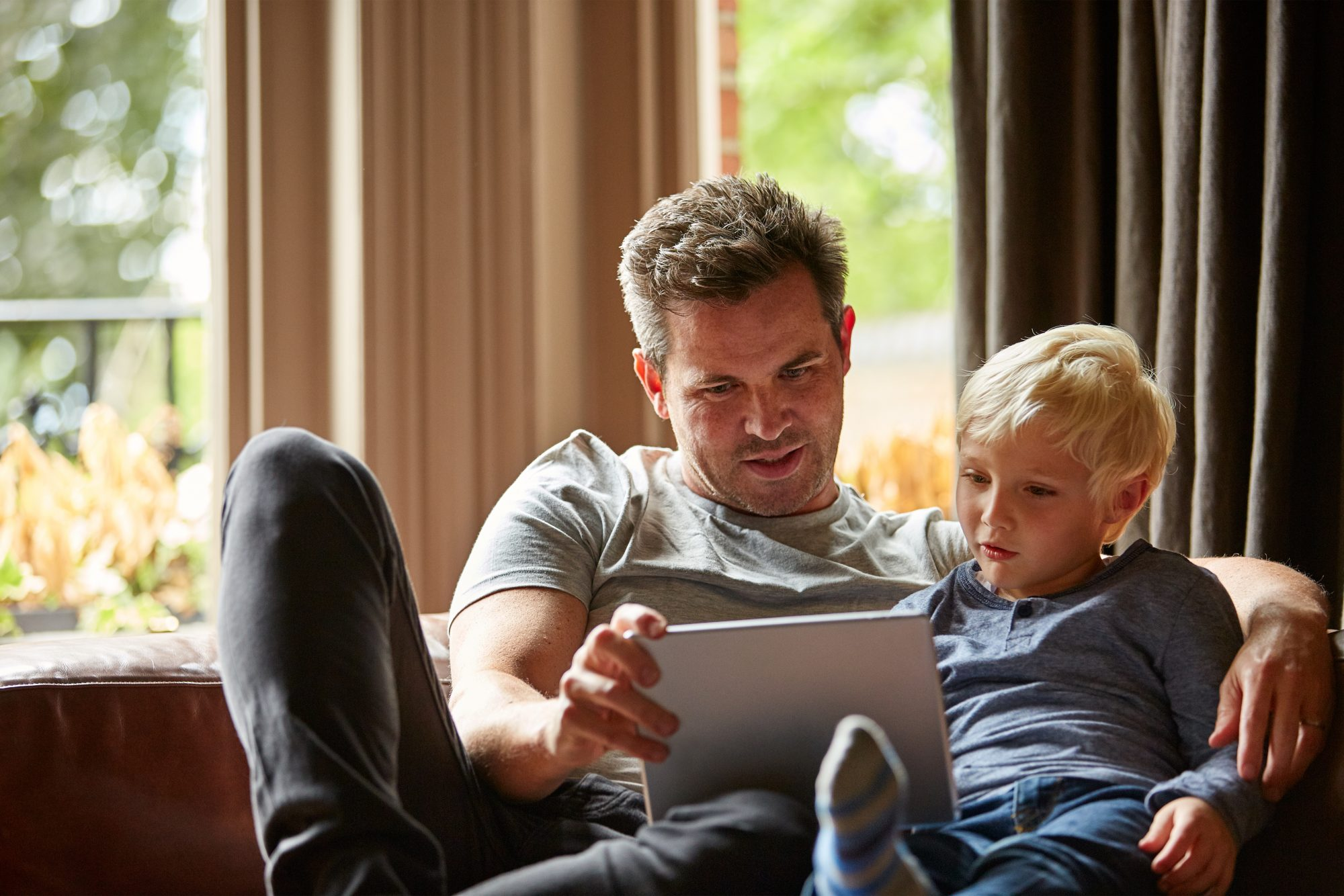 Middle aged man sitting with young son looking at a tablet.