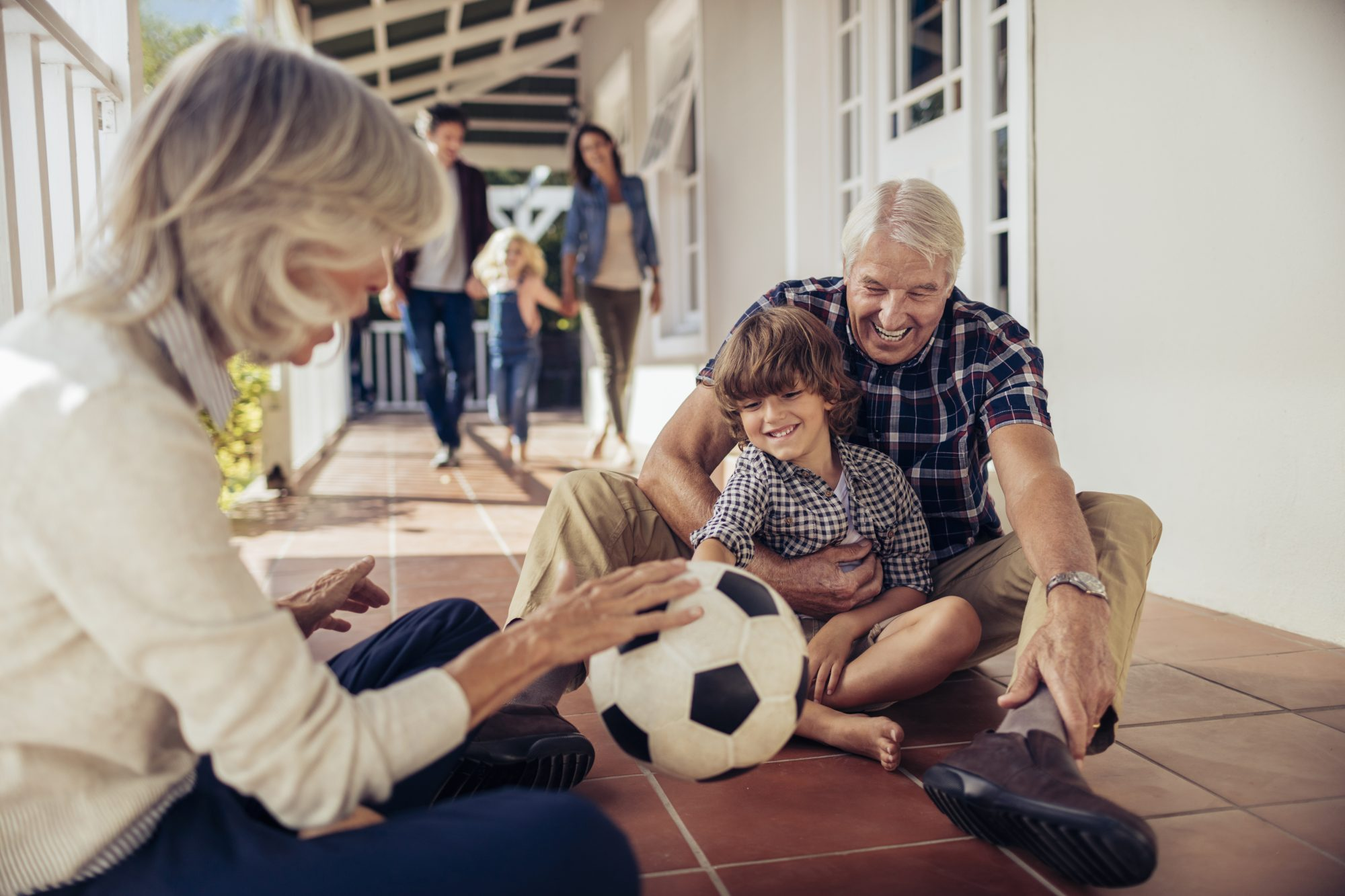 Grandfather and grandmother play soccer with their grandson on the patio while the rest of the family comes to join them.