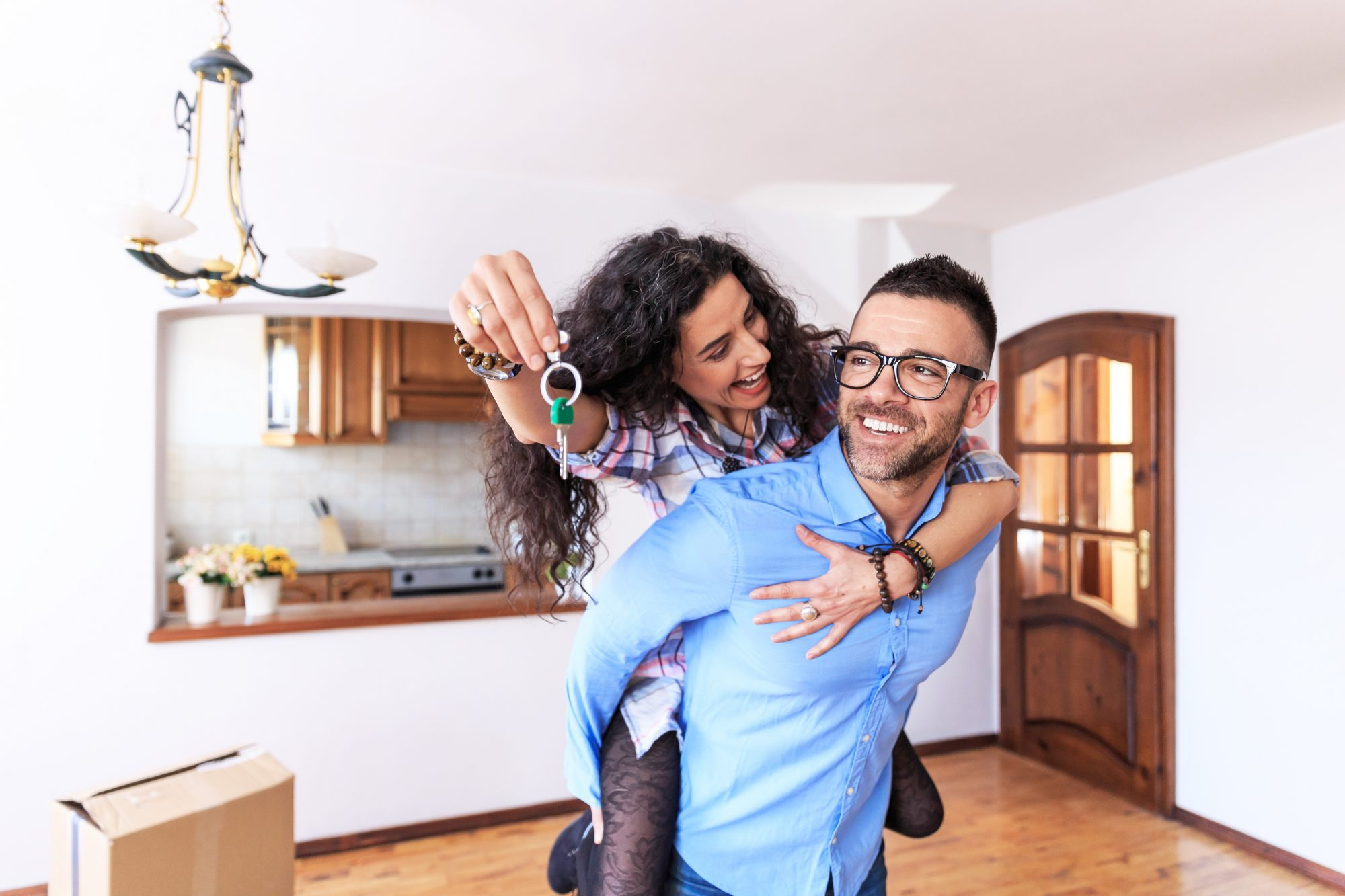 Woman piggyback's on husband while holding their new house key in her hand.
