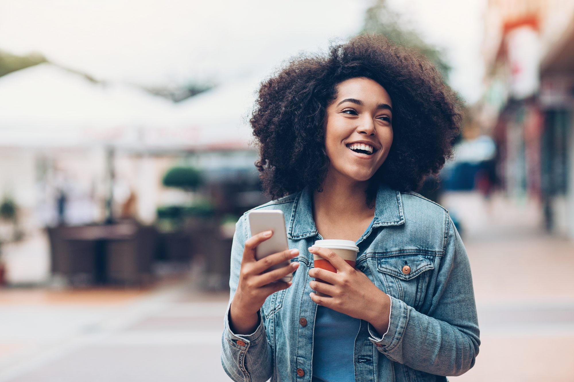 Young woman smiling with coffee and cellphone in her hand.