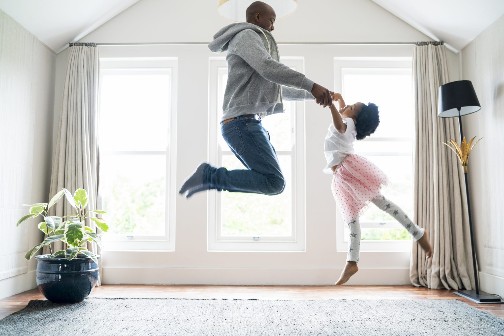 #2 Father and young daughter dance together in their home on a sunny day.