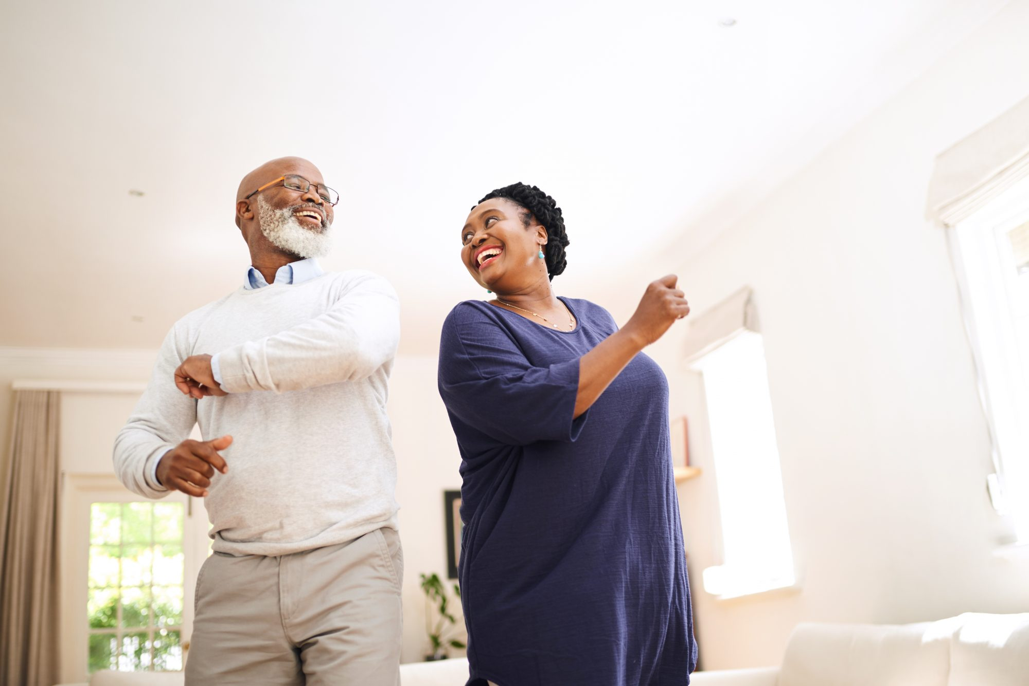 Mature couple dance together in their living room.