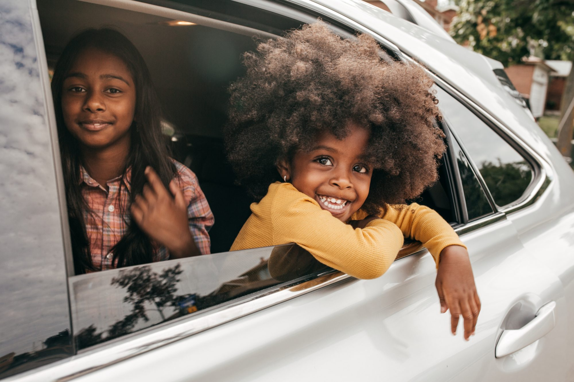 Young children sitting in the backseat of family vehicle while taking a drive on a summer day.