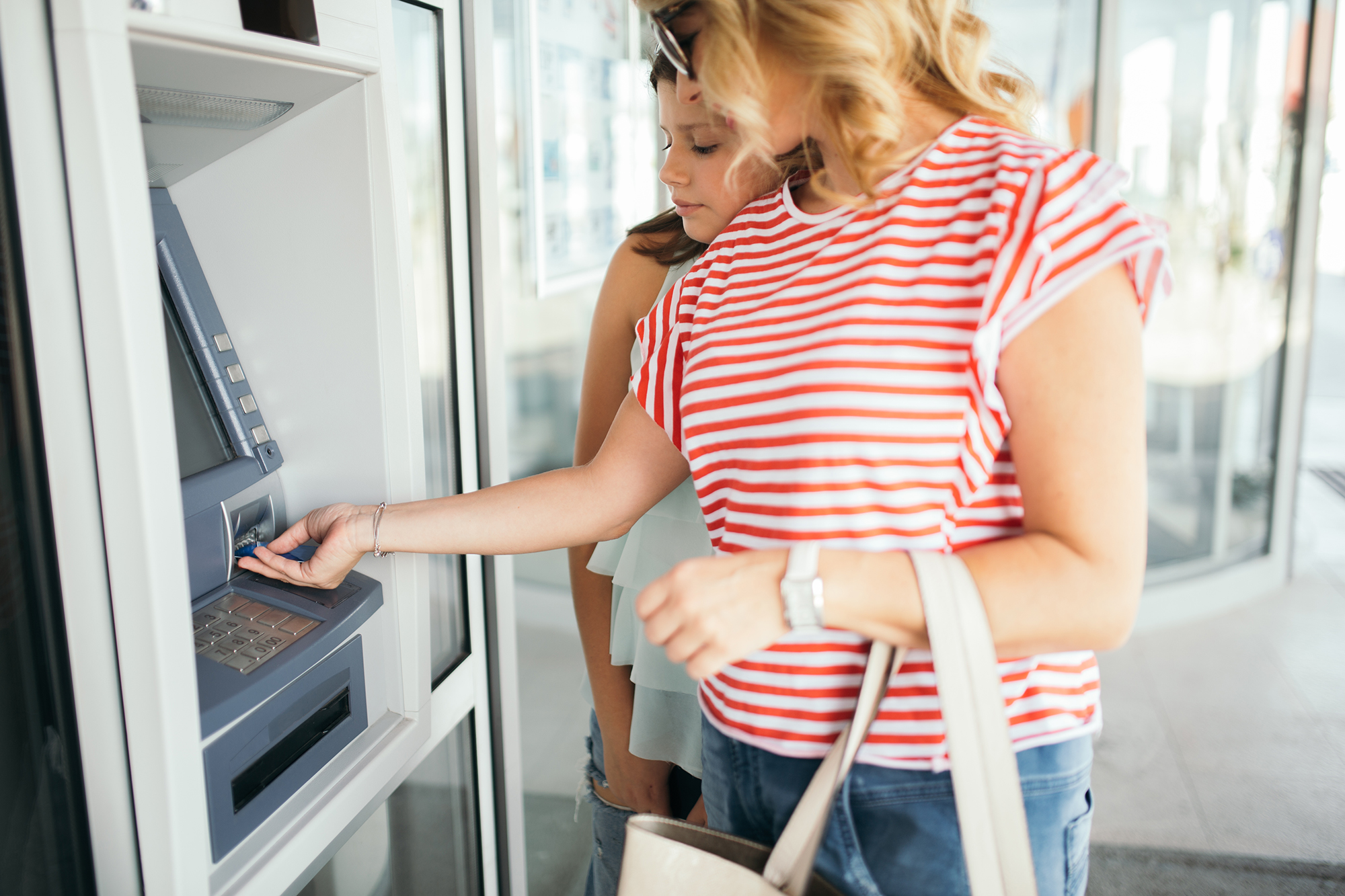 Older sister with younger sibling walks up to an ITM to make a transaction on a sunny summer day.