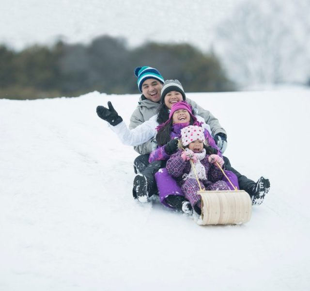 Family sledding down a snow covered hill during winter.