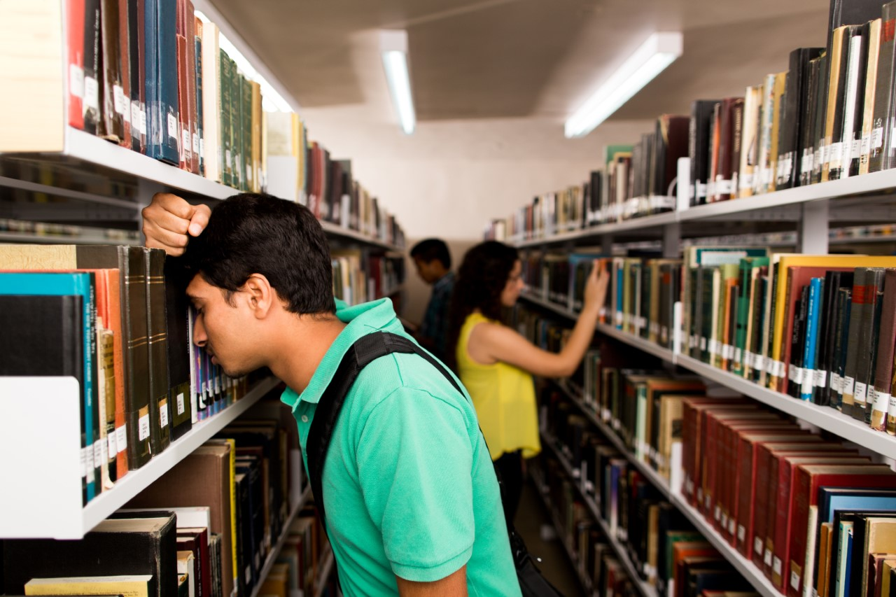 young male student frustrated in library with head against bookcase