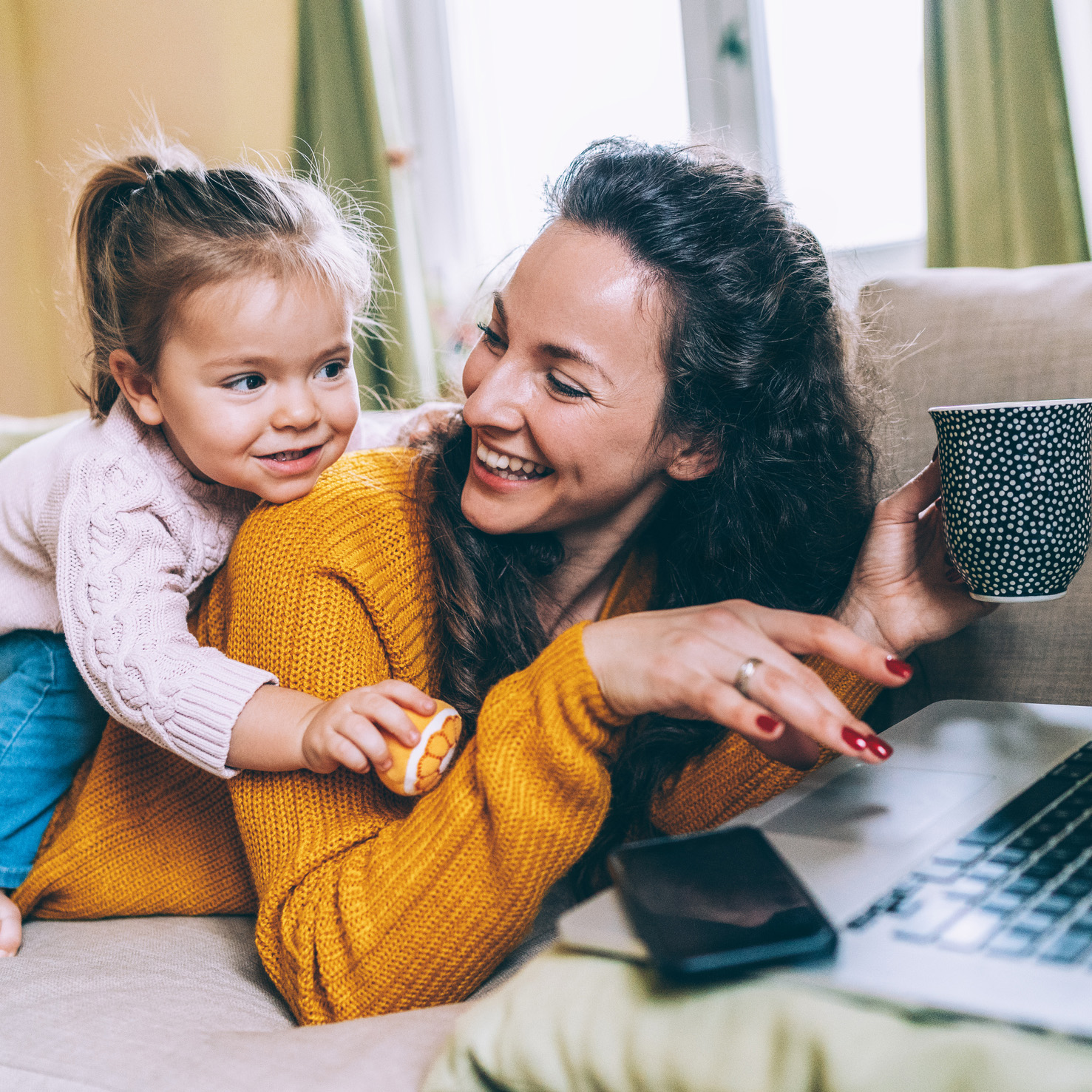 Young daughter distracting mother who is working from home