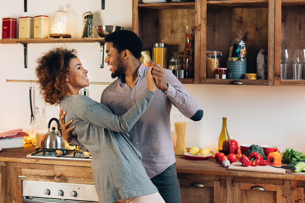 Young african-american couple in love dancing in kitchen