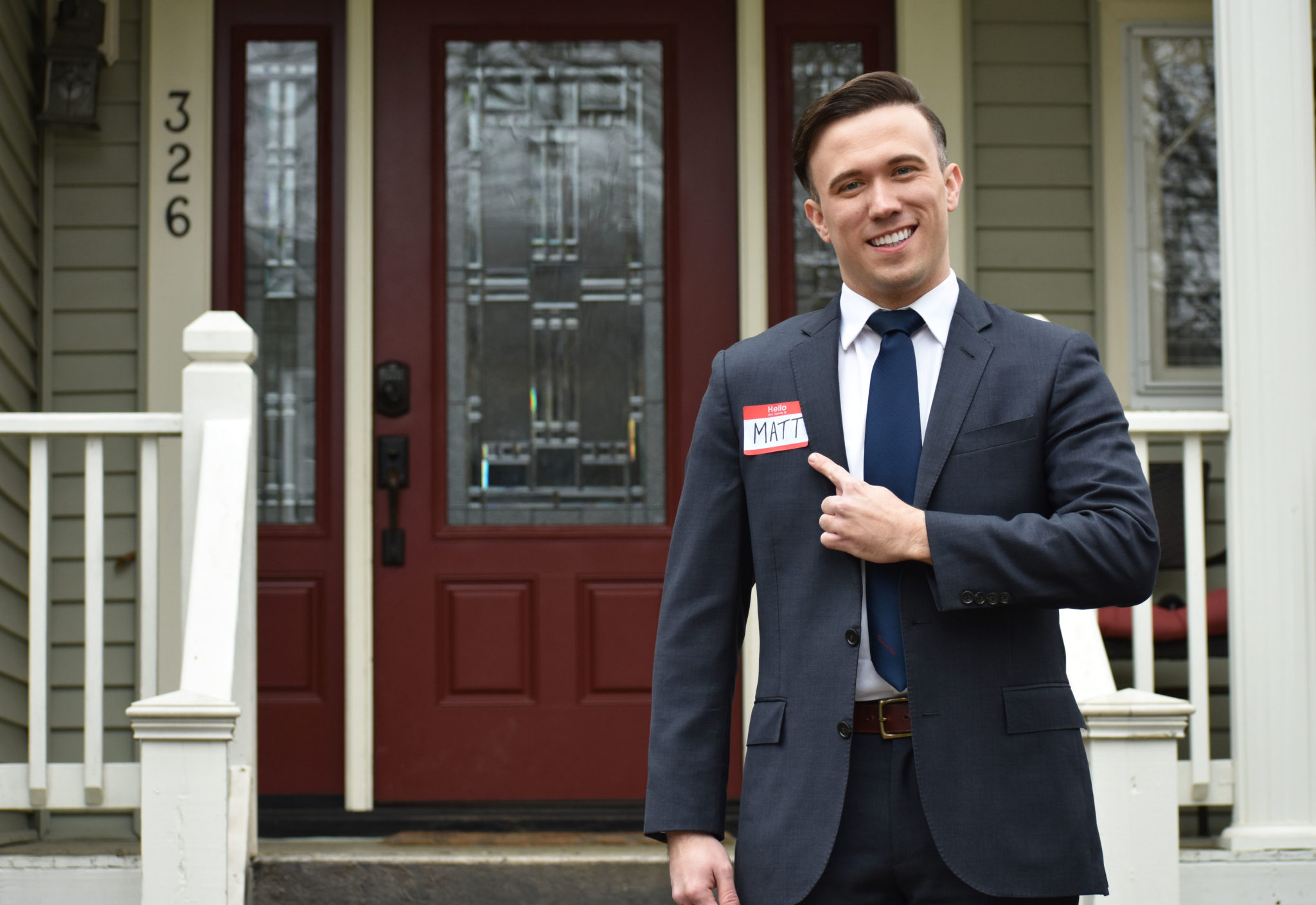 Realtor in a suit standing at the front door of home for sell while pointing to his name tag that states