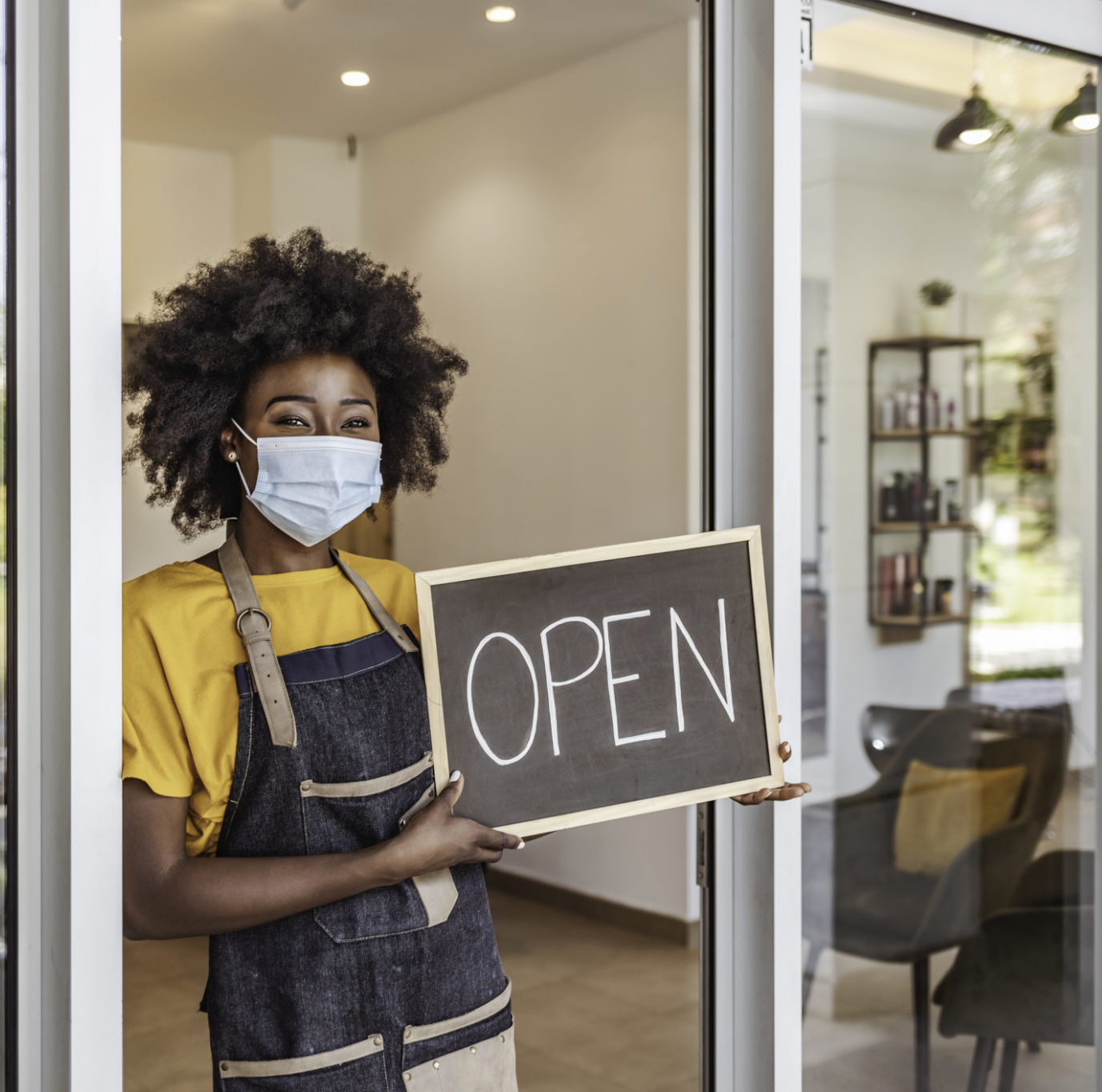 One African-American Woman with surgical protective mask holding open sign in front of her small business store.